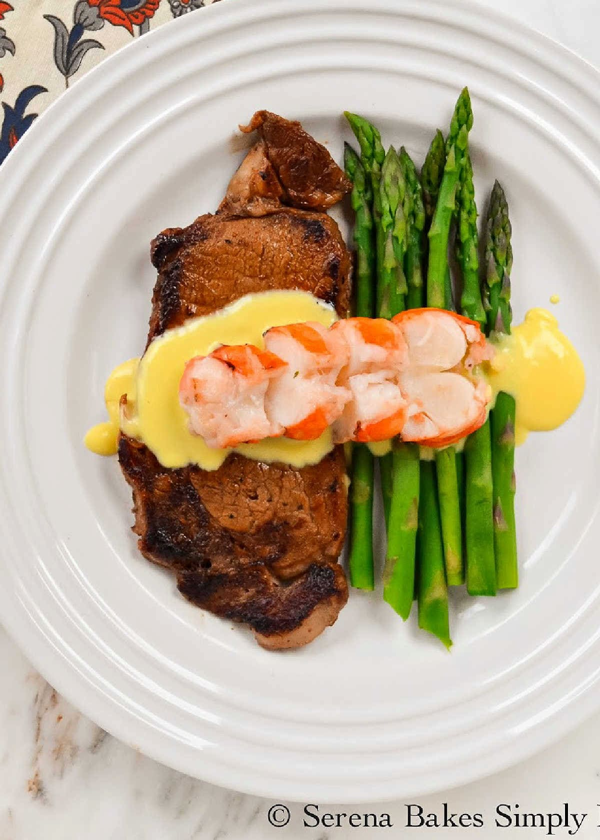 Perfectly Pan Seared Steak covered with Hollandaise Sauce and Sliced Lobster Tail with Asparagus on the side on a white plate.