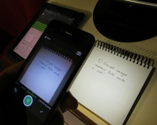 Fotografia mostrando o momento em que o smartphone fotografa um bloco de notas com a anotação do telefone