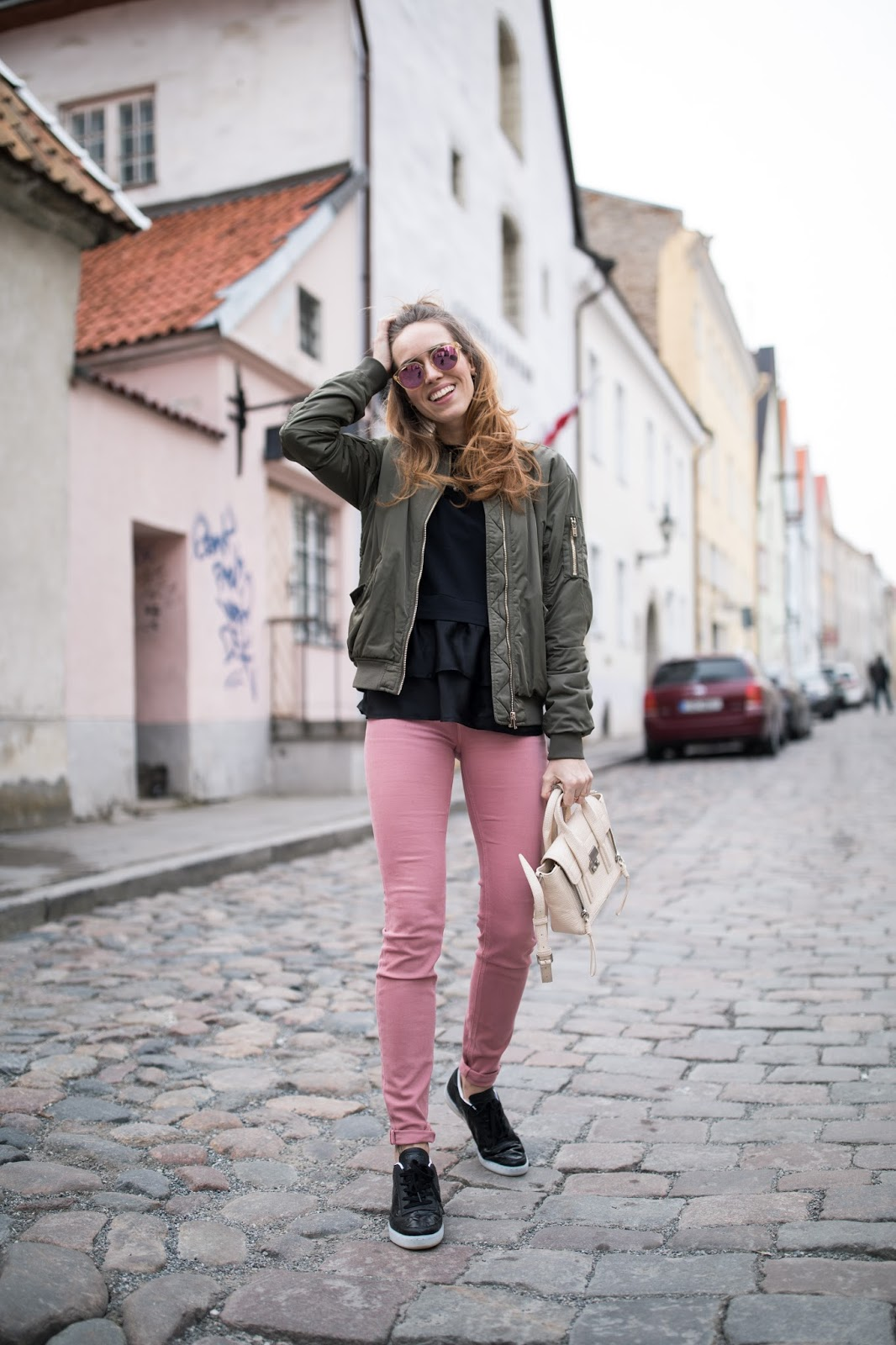 green bomber pink jeans black sneakers outfit