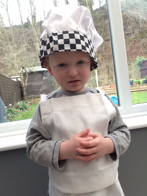 Grumpy looking little boy dressed as a chef.