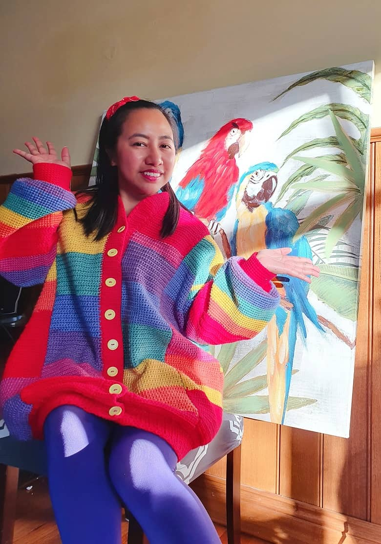 a picture of a girl wearing a crocheted rainbow jumper, sitting next to painting of a parrot