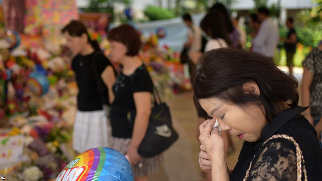 Sarah Kee, 61, of Singapore, wipes her tears at an area set aside for tributes to former Singapore Prime Minister Lee Kuan Yew at the hospital where he passed away, Monday, March 23, 2015 in Singapore.