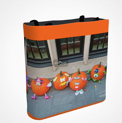 "This screen-shot features an orange tote/bag/pouch which has an image imprinted on it that shows five pumpkins sitting on a sidewalk alongside a building in NYC. Each pumpkin has a face painted on it and they also each have hands and feet attached to them which are made from an unidentified material used in craft making. These pumpkins could easily be thought of as carolers! The tote/bag/pouch is available in three sizes (13"" by 13"", 16"" by 16"" and 18"" by 18"") and can be purchased via Fine Art America @ https://fineartamerica.com/featured/the-pumpkin-choir-patricia-youngquist.html?product=tote-bag"