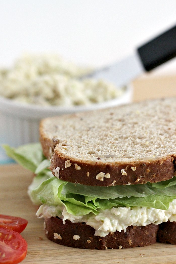 Southern Style Chicken Salad sandwich on wooden board with bowl of chicken salad in the background