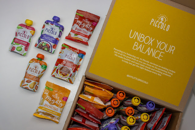 An open delivery box received to review with baby pouches a meal pouch and toddler snacks
