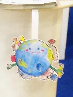 展示台のテーブルからぶら下がる地球くんPOPの写真