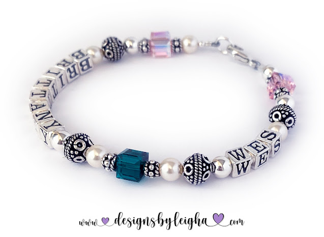 This Pearl and Swarovski Crystal Birthstone Mom Bracelet is shown with a lobster claw clasp and 2 names and 3 birthstones: October/Opal - Brittany - May/Emerald - Wes - October/Opal