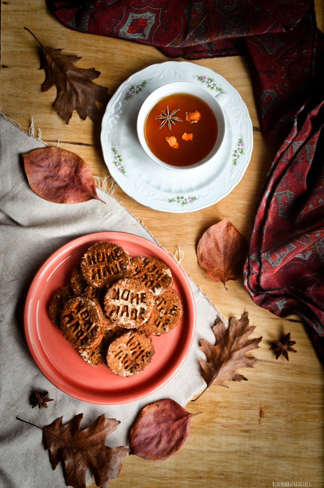 Vista cenital, seevilleta vintaje burdeos, taza porcelana antigua con té, Galletas caseras sobre plato cerámica rojo, fondo madera oscuro, manzanas rojas, hojas secas otoño, paño de lino beige