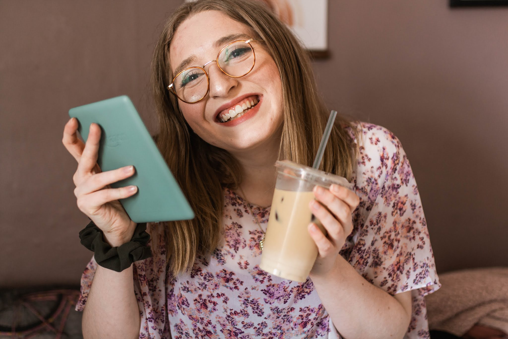 girl smiling while holding sage kindle paperwhite and iced coffee latte