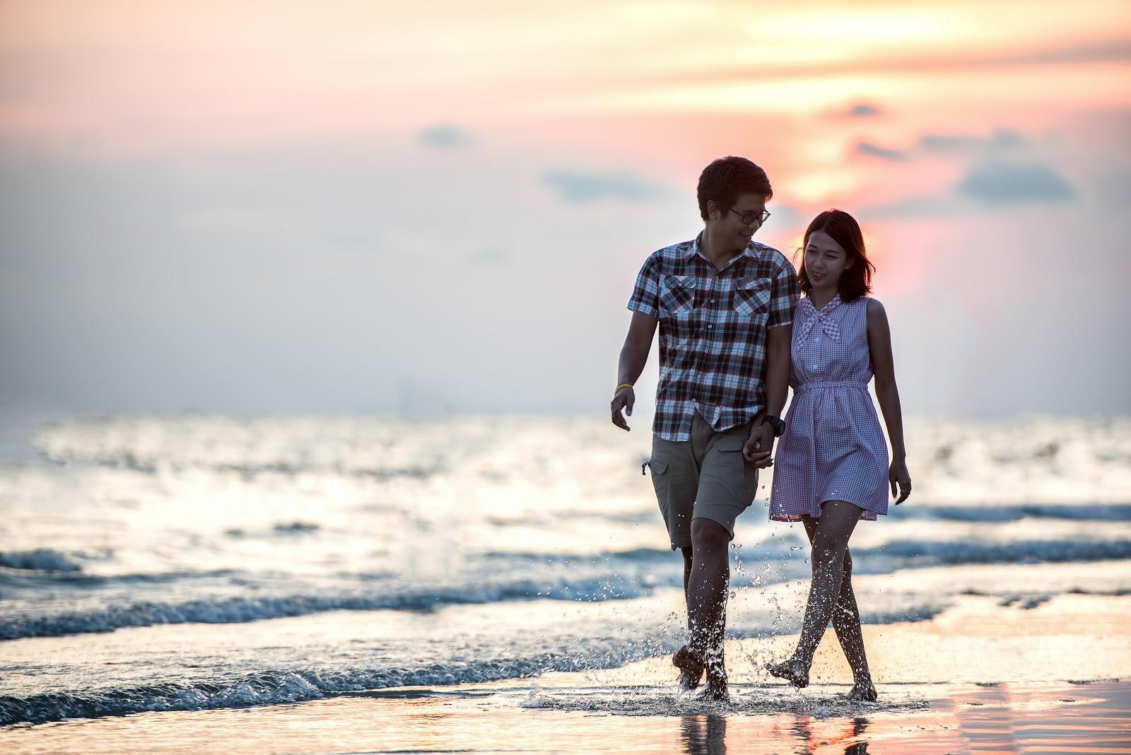手を繋いで海辺を歩く男女のカップル