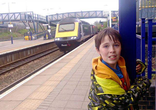 A boy at a train station with a train in the background