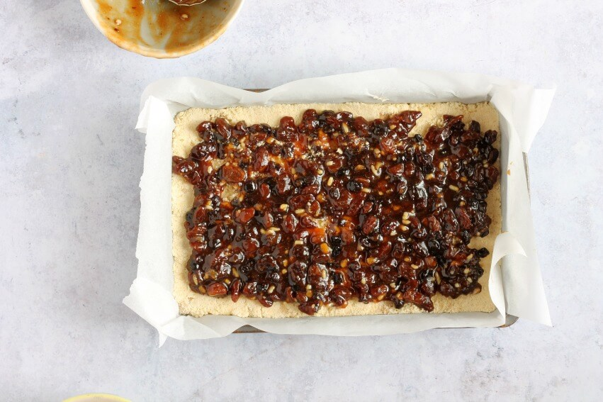 Spreading mincemeat onto crumble base