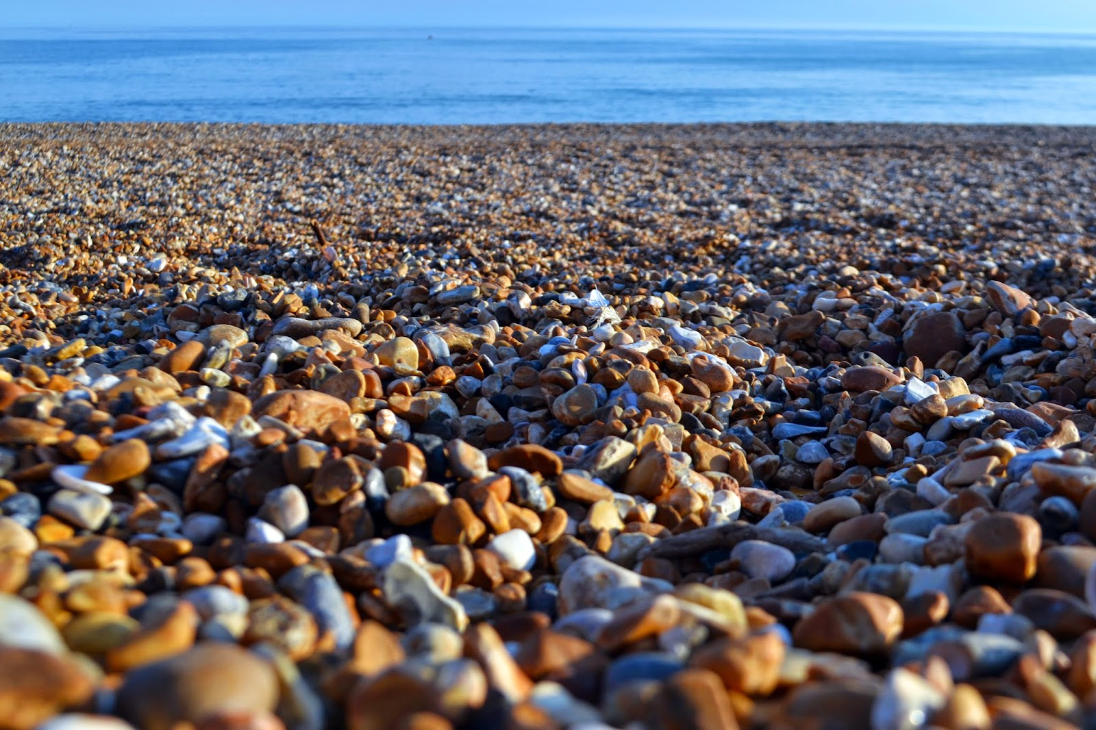 a close up shot of the pebbles on Bognor Regis Beach, the ocean has been seen out of focus in the background