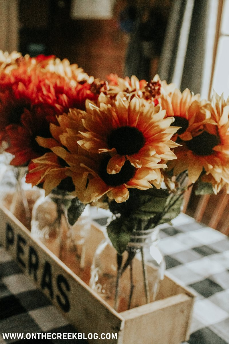 A simple fall centerpiece made with an old crate, mason jars, & Dollar Tree flowers! | On The Creek Blog