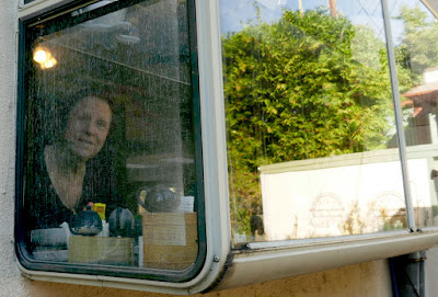 Leslie peering out through the kitchen window