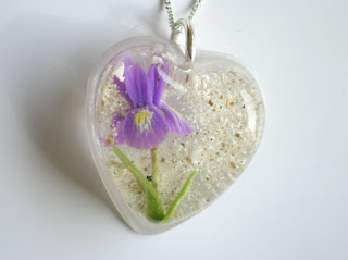 Memorial pendant containing ashes and an Iris flower
