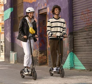 Two adults riding electric scooters