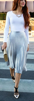 Saia plissada prateada com malha branca e colar curto.