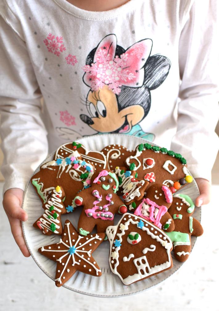 Galletas de jengibre para Navidad, una niña sostiene un plato con galletas
