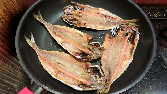 フライパンにサラダ油をまわし入れ、中火にかけたらアジの干物を皮を下にして重ならないように並び入れます。