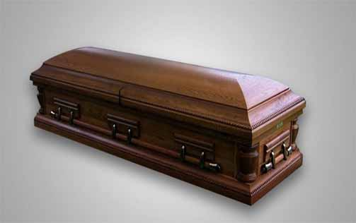 A brown coffin on the floor covered
