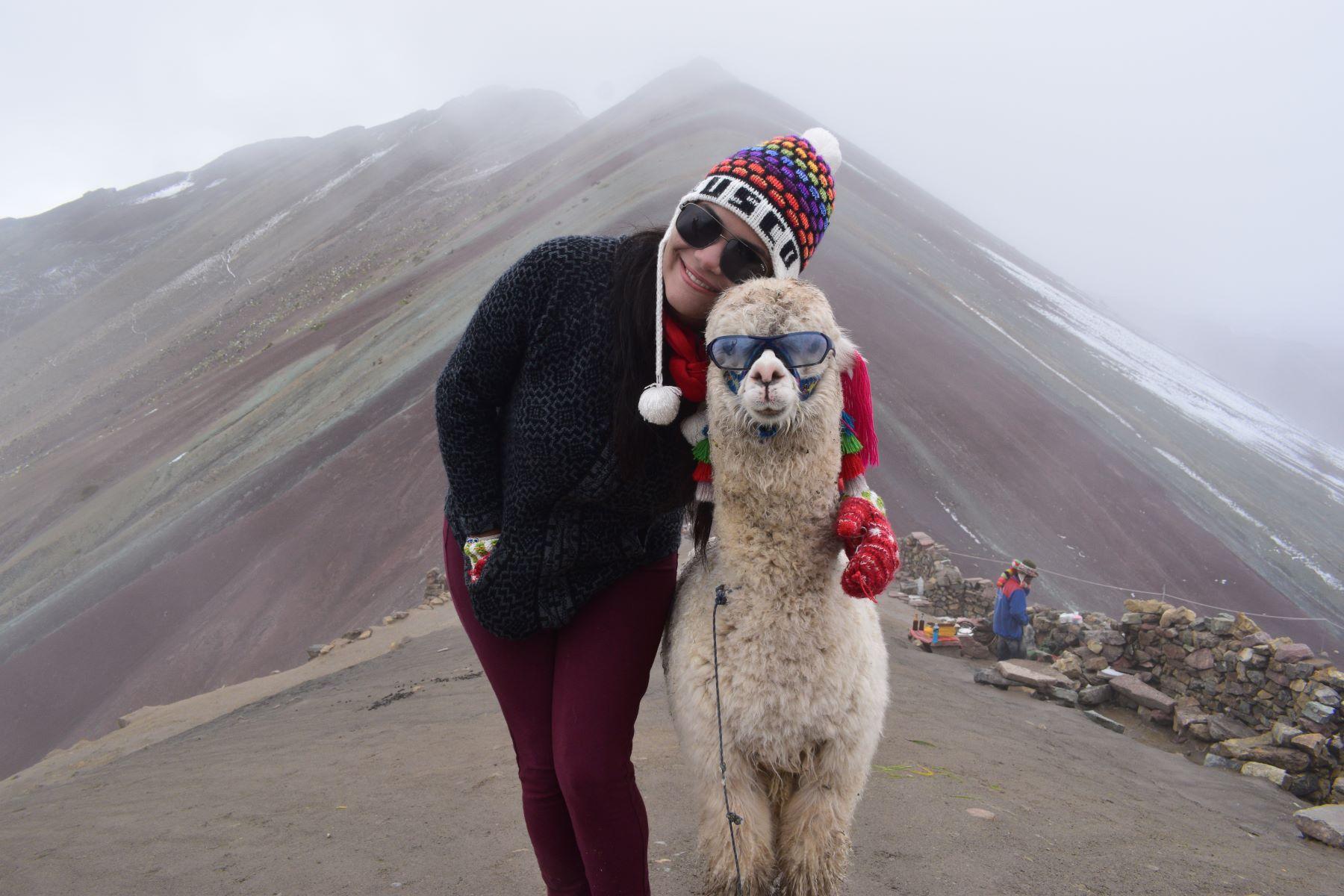 mulher jovem abraçando uma llama peruana