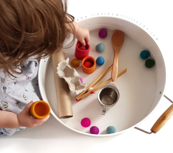 toddler colour sorting with pom poms and grimms wooden bowls