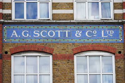 Photograph of a section of brick facade. There is a tiled sign: inside a green border is a blue background with white lettering saying 'A. G. SCOTT'. Above the sign are the bottoms of two windows and the brick is in red and white stripes. Below are the tops of two windows with curved top edges, and the wall is all red brick.