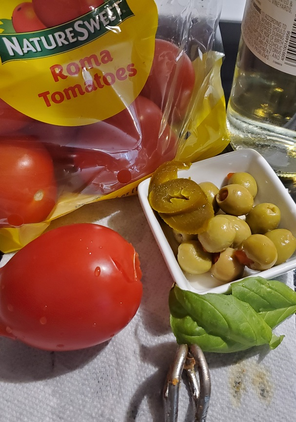 tomatoes, olives, peppers, onion and garlic used in making pork sazon