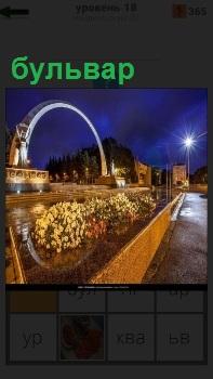 В вечернее время бульвар с освещением, цветами и аркой в середине вход в парк