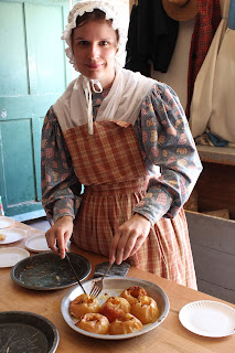 A woman in early 19th century period dress serves slicees of baked apples from a piepan.