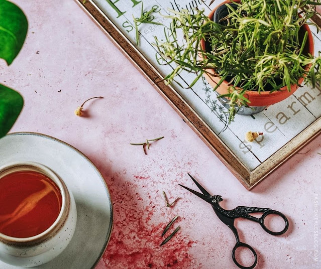 Herbal tea on pink surface with scissors