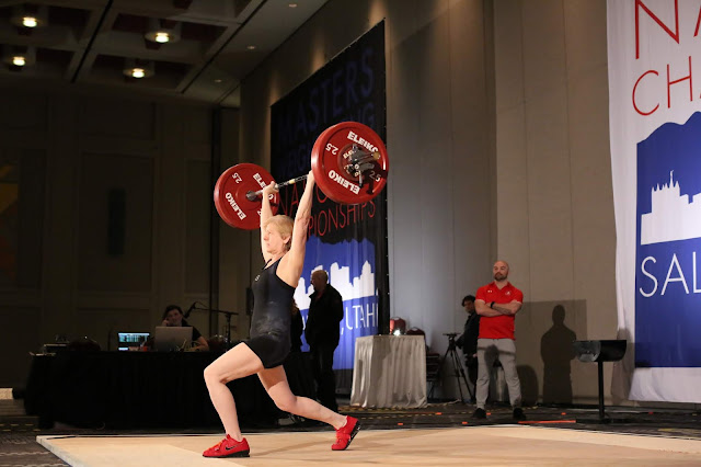 Woman lifting barbell over her head
