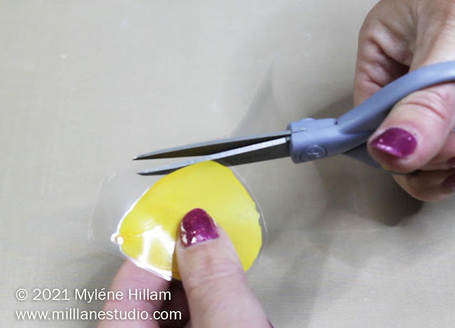 Scissors trimming a yellow rose petal encased in a laminating pouch close to the petal