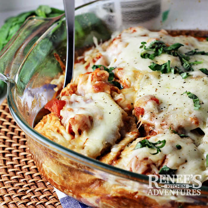 Baked Eggplant Parmesan in casserole dish, ready to serve, with serving spoon