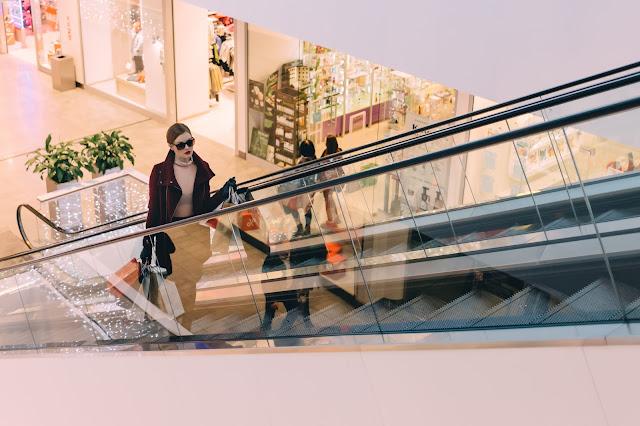 Beautiful chic woman riding the escalator at a mall.