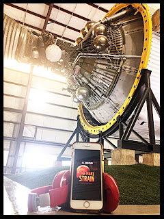 Inside the Johnson Space Center, the tail end of a rocket with a yellow ring at the base, propped up by thick, black steel, sunlight streaming in through the thin slits of windows, and on the ground is a pair of red Beats headphones and an iPhone playing the audiobook The Mars Strain with the image of the Red Planet in the background.