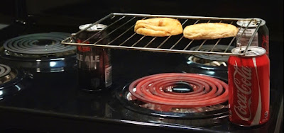 Toasting a bagel on a small rack on 3 beer cans over stove heating element