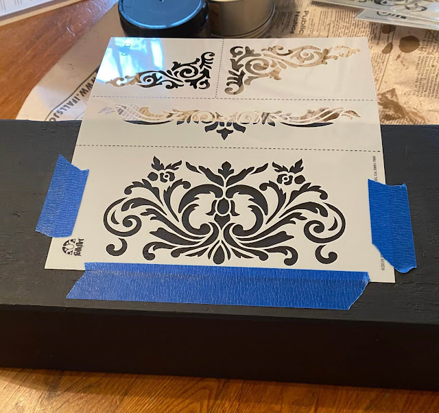 Photo of stencil taped to painted flower box