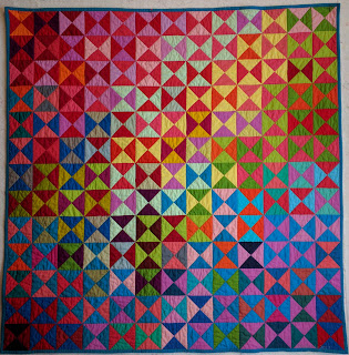 The colors of a wide variety of solid fabrics sweep across the surface of this quilt. Pink, orange, red, brown, blues, green, and yellow are included.