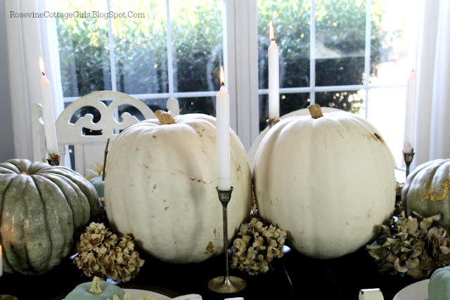 Close up of large pumpkins and dried hydrangea flowers decorating a table | rosevinecottagegirls.com | A farmhouse thanksgiving tablescape | how to decorate a thanksgiving table