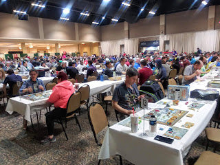 The main convention hall. A large area filled with tables, with most of the seats taken by people playing board games.