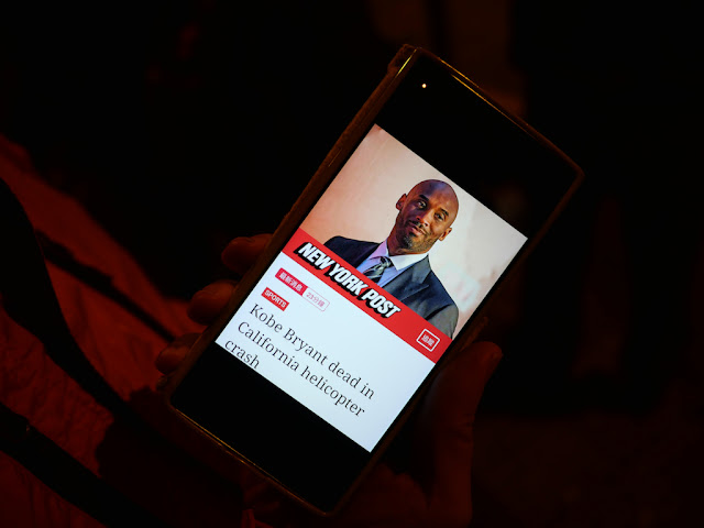 mobile phone displaying New York Post article on Kobe Bryant's death