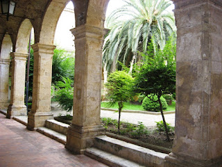 The archways and cool greenery in the cloisters in Altomonte, Calabria, Italy.