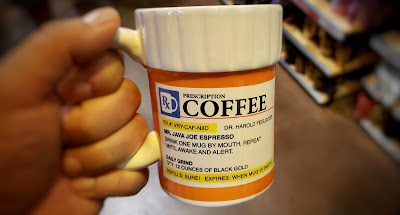 Picture of a person holding a mug, which has a filled out prescription for taking Coffee.