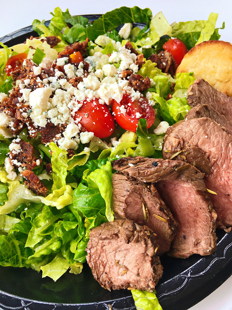 The Bistro Steak Salad at Ashely Macs in Birmingham, AL is incredible! Grilled petite tenderloin, cherry tomatoes, bleu cheese, grilled red onions, and garlic croutons. Served over a bed of mixed greens with our Balsamic vinaigrette and creamy horseradish dressing and a sour cream biscuit.