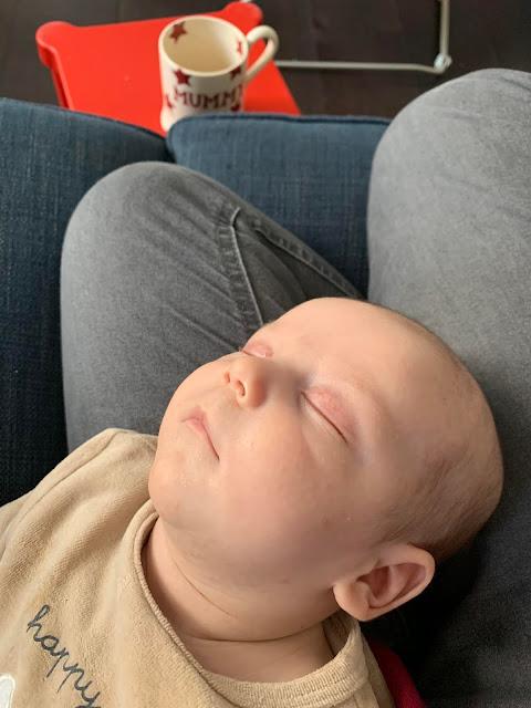 Newborn baby boy asleep with head in mum's lap