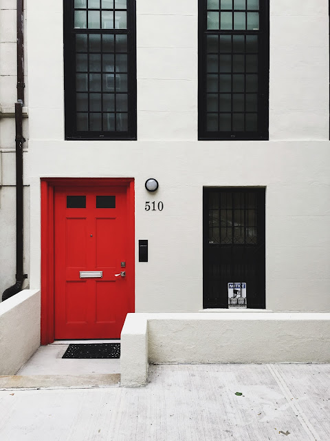 red door on a white building, unsplash.com