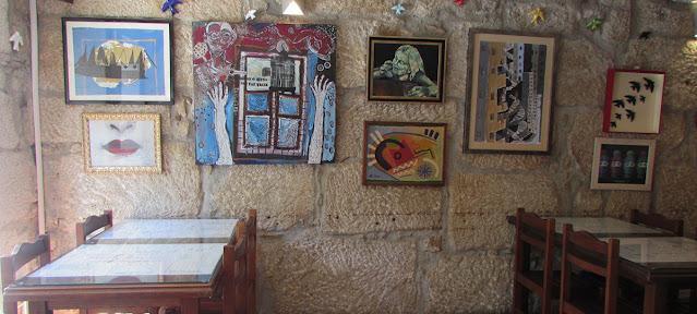 mesas de restaurante e vários quadros de arte na parede