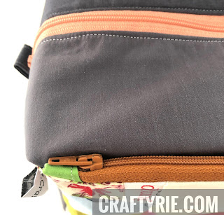 Front zipper view of boxy pouch with tag showing